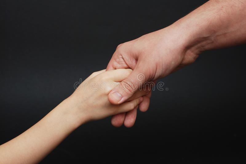 Father giving Hand to a Child. Parental Relationshipp, closeup. Isoalted on Black Background. stock images