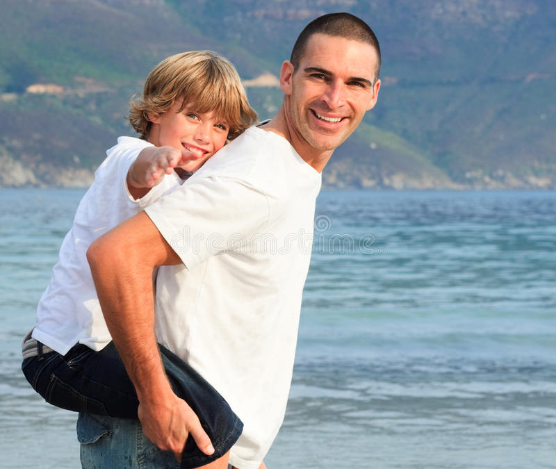 Father Giving His Son Piggyback Ride On The Beach Stock