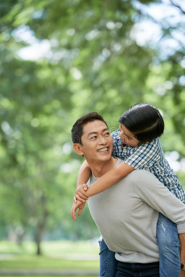 Father giving piggyback ride royalty free stock photography