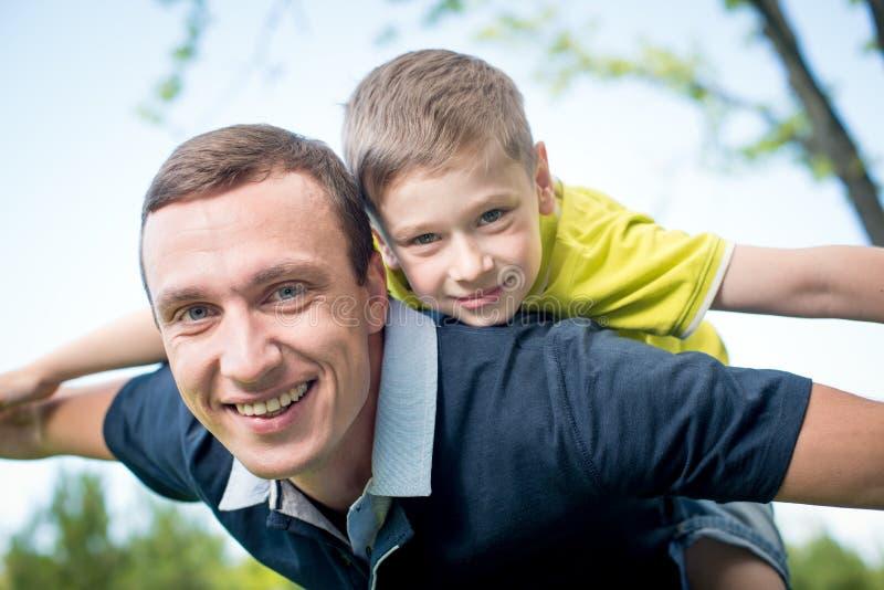 Father giving piggyback ride to his son stock photos