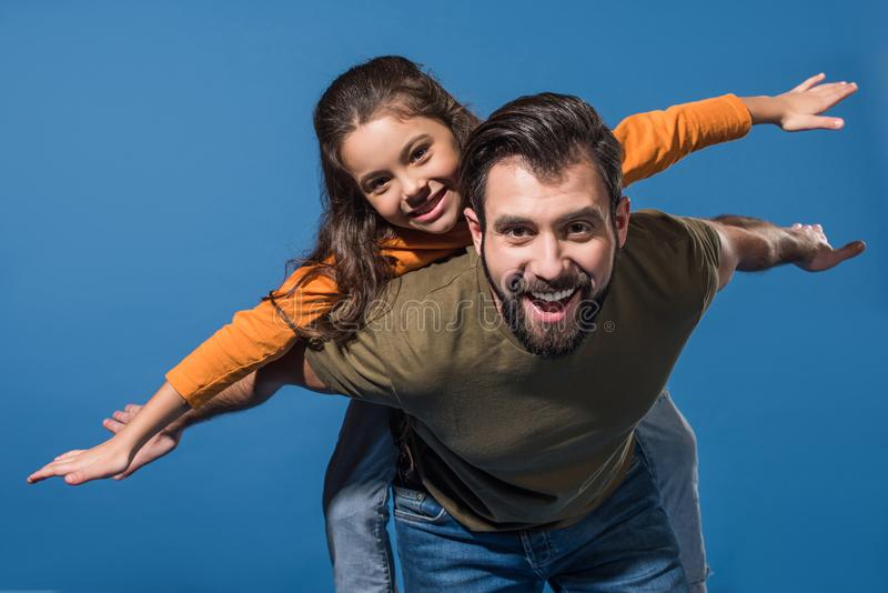 father giving piggyback to daughter stock photography