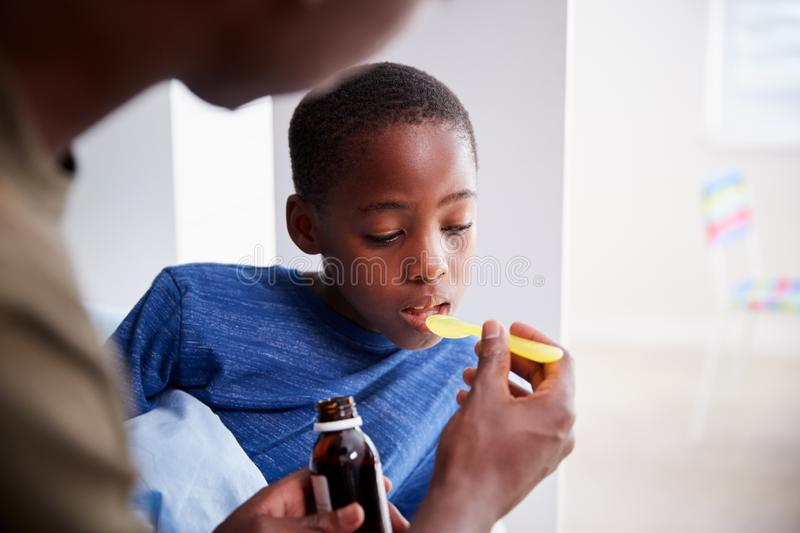 Father Giving Sick Son Ill In Bed Medicine From Bottle stock images