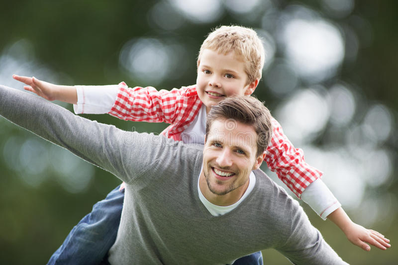Father Giving Son Piggyback In Countryside royalty free stock image