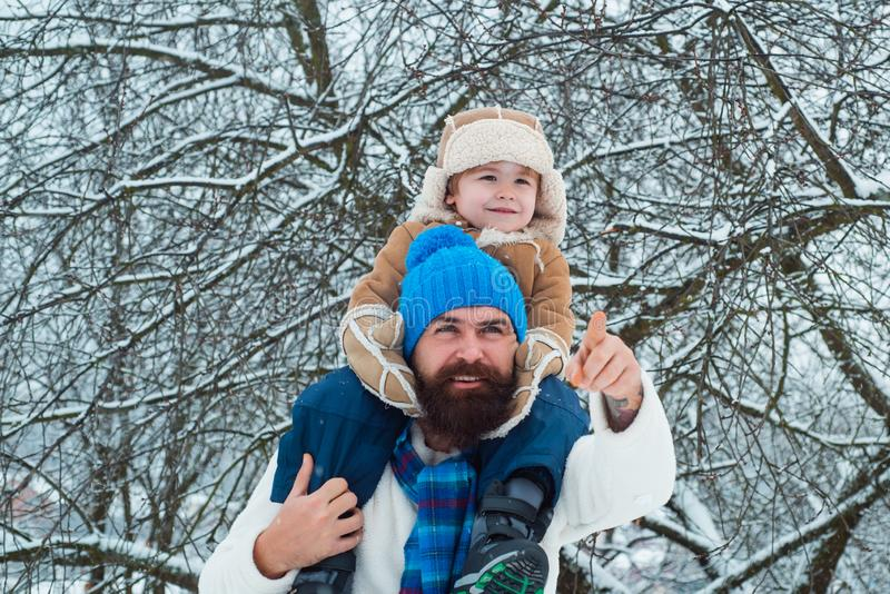 Father giving son ride on back in park. Child sits on the shoulders of his father. Portrait of happy father giving son. Piggyback ride on his shoulders and stock photo