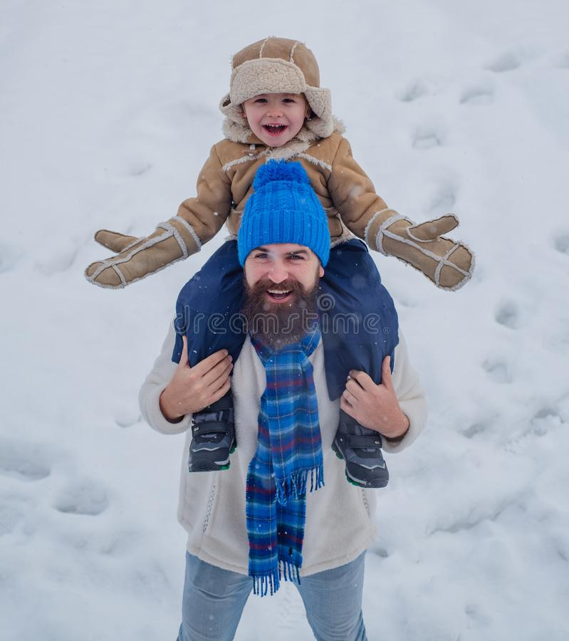 Father giving son ride on back in park. Merry Christmas and Happy New Year. Portrait of happy father giving son. Piggyback ride on his shoulders and looking up stock photo