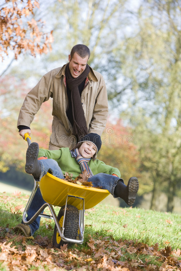 Father giving son ride in wheelbarrow royalty free stock image