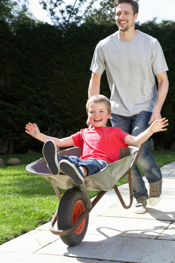 Father Giving Son Ride In Wheelbarrow stock photo