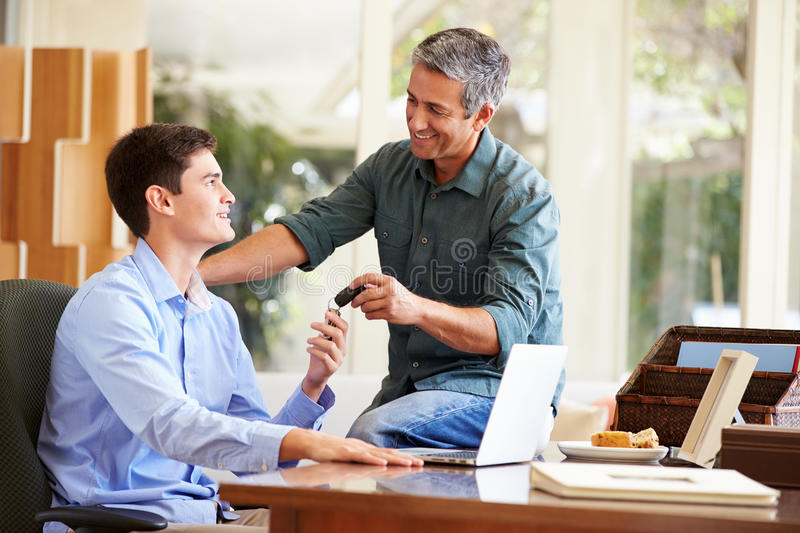 Father Giving Teenage Son Car Keys. Smiling At Each Other stock photography