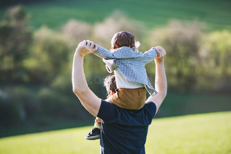 A father giving toddler son piggyback ride outside in spring nature. royalty free stock photo
