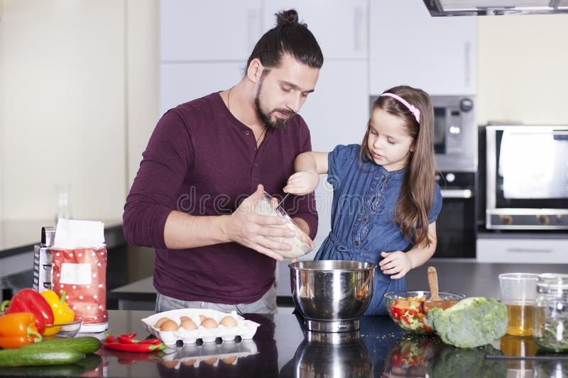 Father and daughter making meal together in kitchen. Cooking classes concept royalty free stock photo