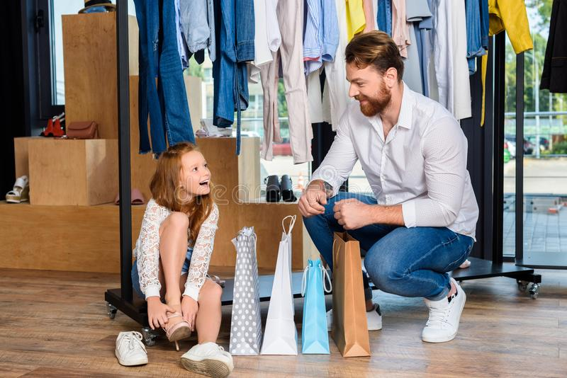Father and happy daughter with shopping bags in boutique with clothes. And shoes royalty free stock images