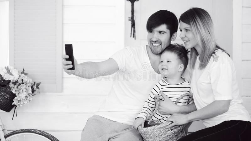 Father of happy family make selfie with his wife and little son in front their home door. In garden royalty free stock images