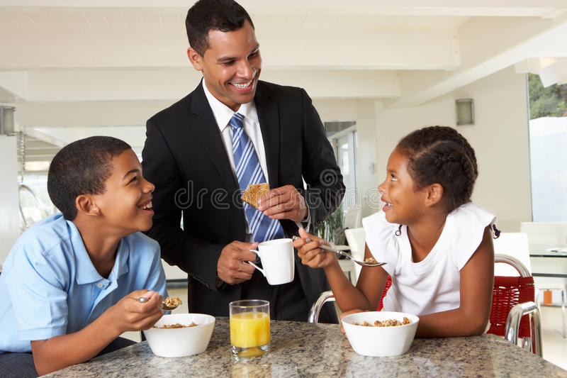 Father Having Breakfast With Children Before Work stock photos