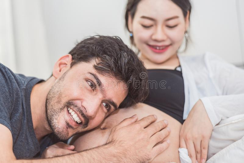 Father hearing his son or daughter kicking sound check inside mother belly when sitting on lying on bed at home. Family healthy. And couples concept. Happy stock photo
