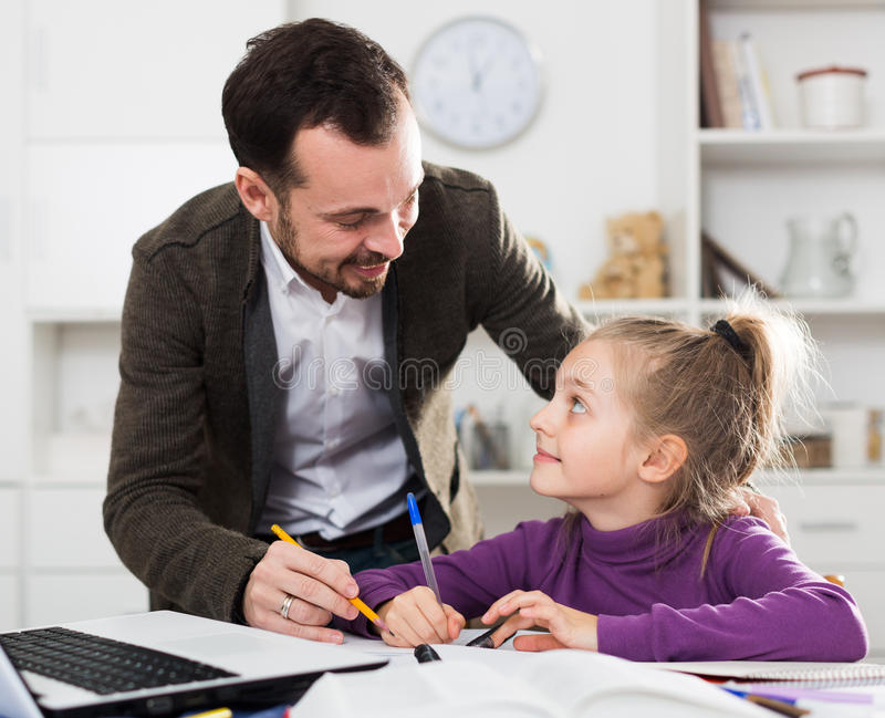 Father helping daughter with homework stock photos