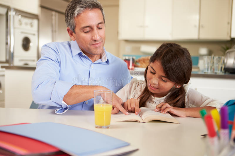 Father Helping Daughter With Reading Homework At T. Able Pointing In Book Sitting Down stock photos