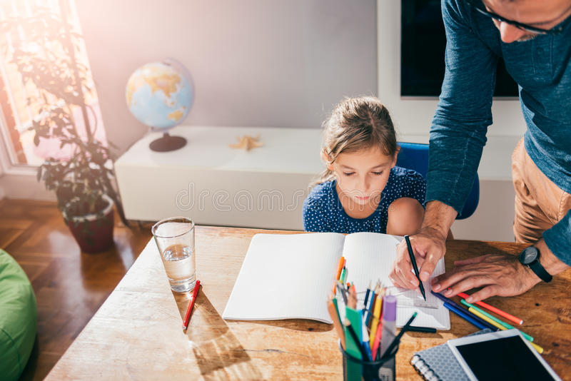 Father helping daughter to finish homework. While using pencil and ruler stock image