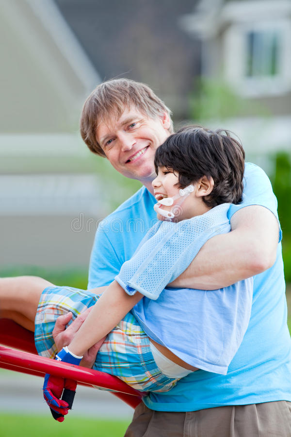 Father helping disabled seven year old son play at playground royalty free stock photography