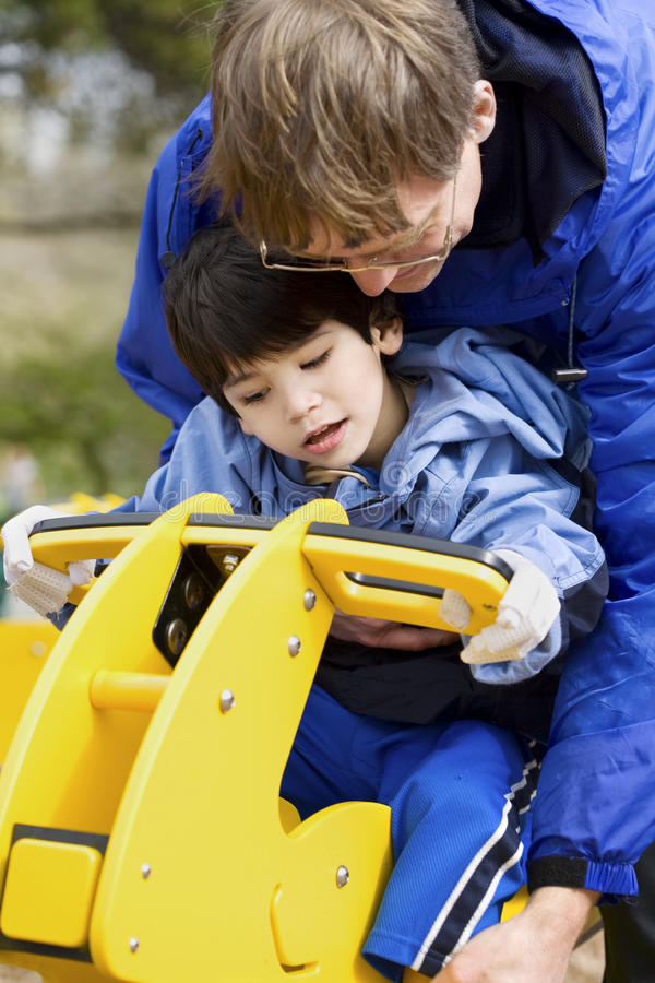 Father helping disabled son play royalty free stock images