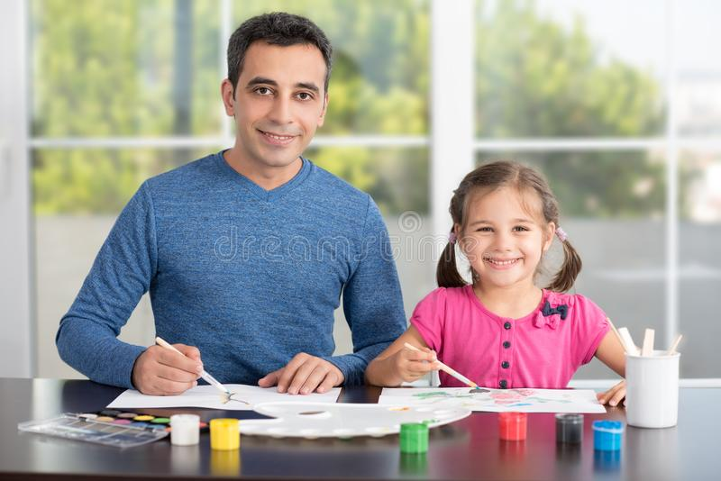 Father Helping Her Daughter Paint Pictures. royalty free stock photography