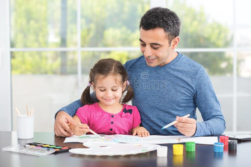 Father Helping Her Daughter Paint Pictures. stock photo