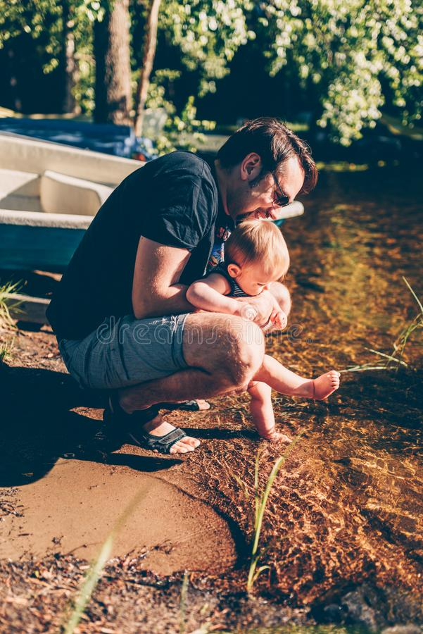 Father helping his baby to test the water royalty free stock image