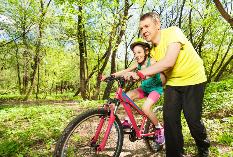 Father helping his daughter cycling in the park. Active father helping his young daughter in helmet cycling the wood's trails royalty free stock image