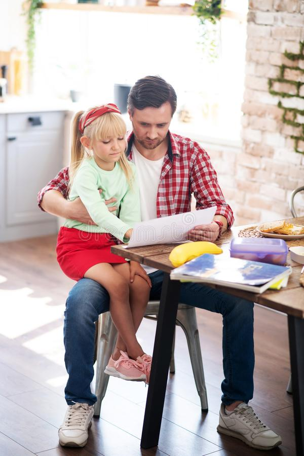 Father helping his daughter with homework after breakfast stock photos
