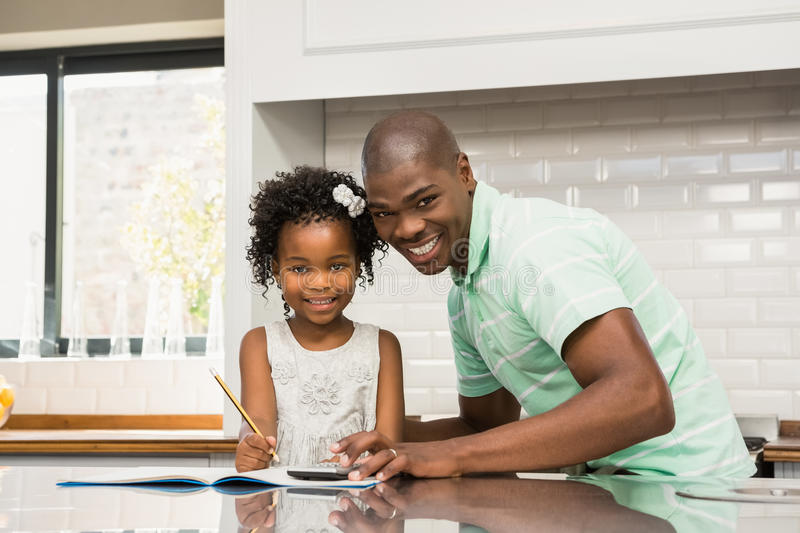 Father helping his daughter with homework royalty free stock image