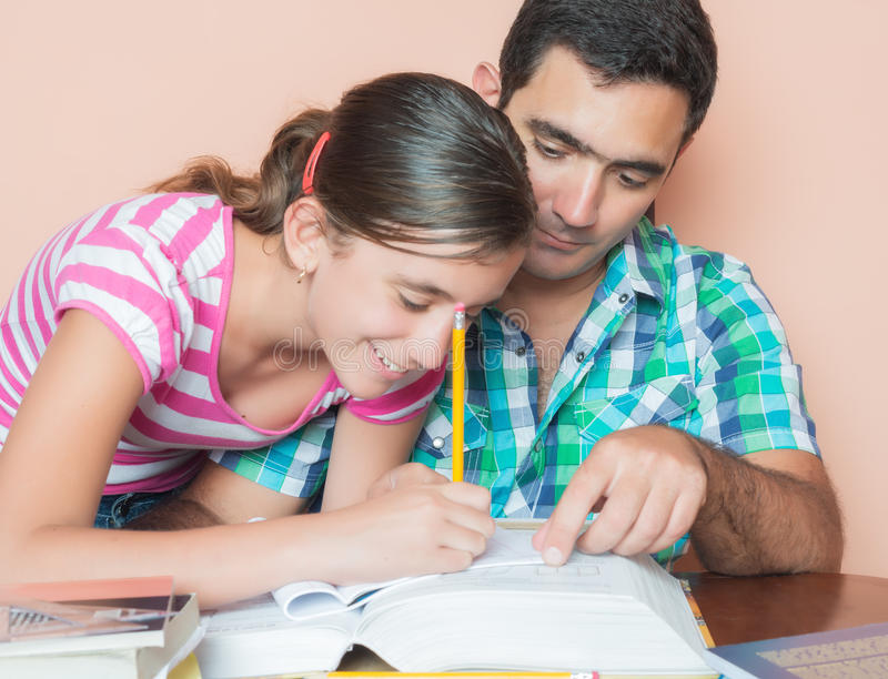 Father helping his daughter to study stock image