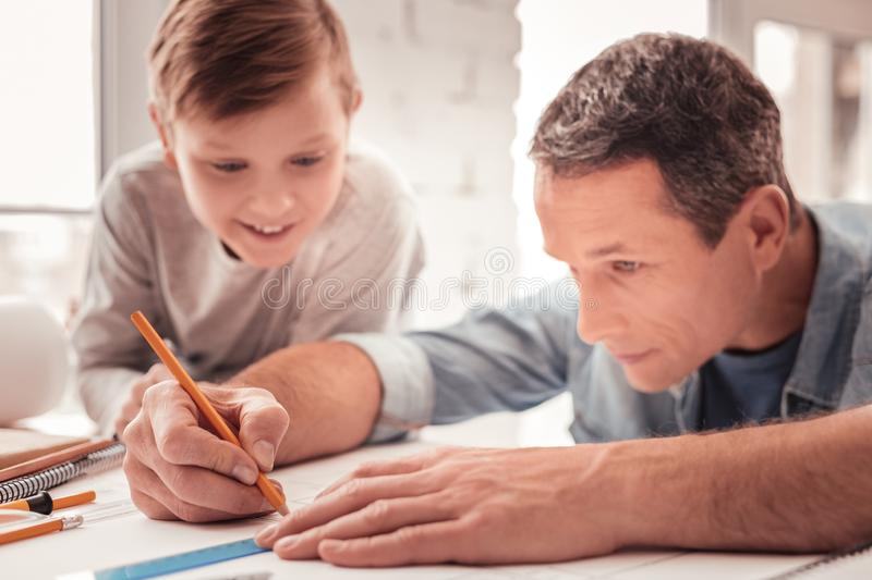 Father helping his son drawing geometrical figures royalty free stock photos