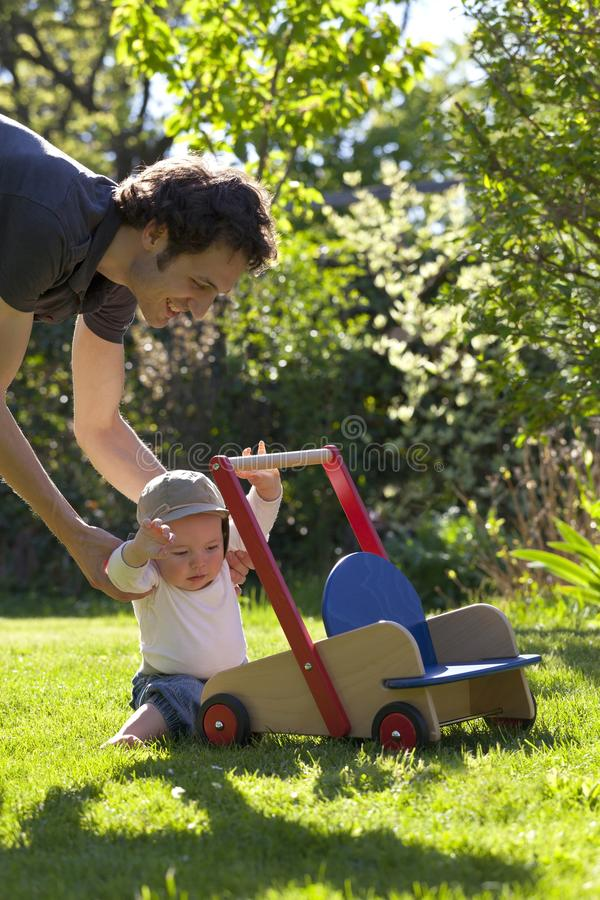 Father helping his son in garden to take his first step of life stock image