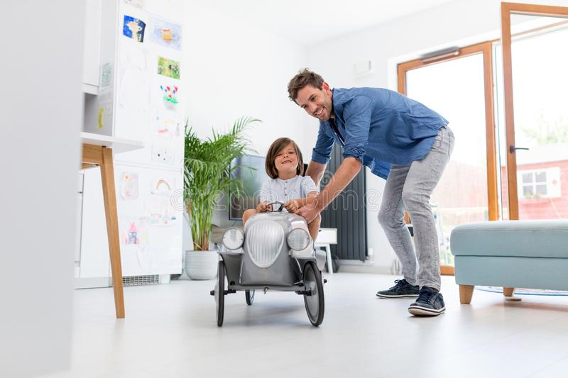 Father helping his son to drive a toy peddle car. At home royalty free stock images