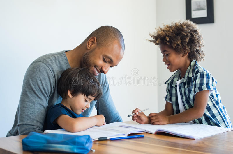 Father helping his sons with homework stock photos