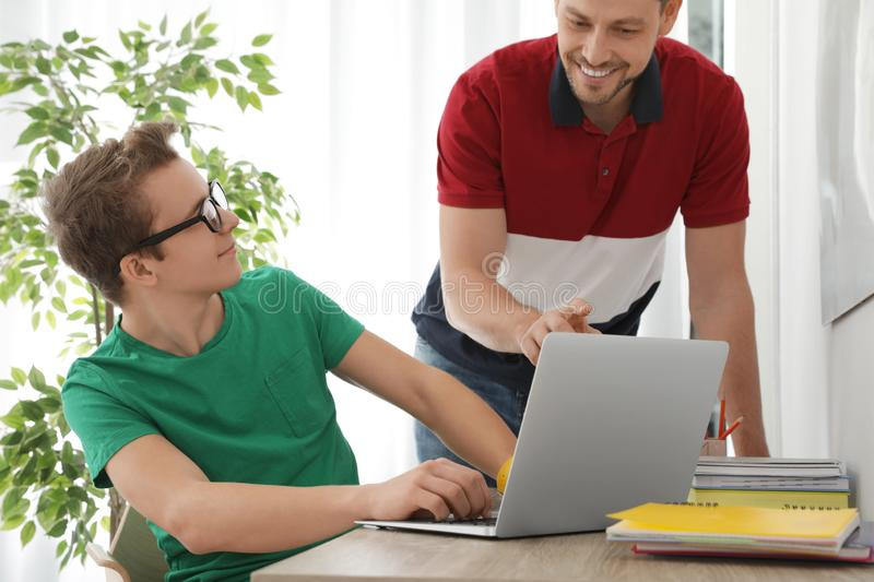 Father helping his teenager son with homework. Indoors stock photos