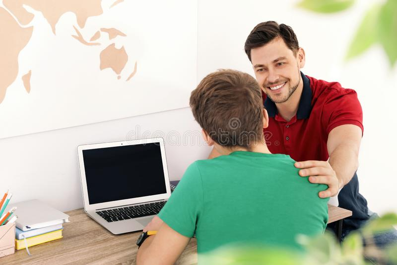 Father helping his teenager son with homework. Indoors stock images