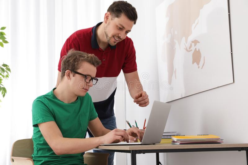 Father helping his teenager son with homework. Indoors royalty free stock photos