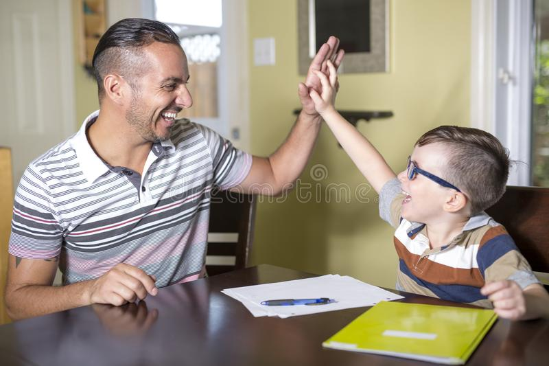 Father helping son do homework. Parent helps his child stock photos