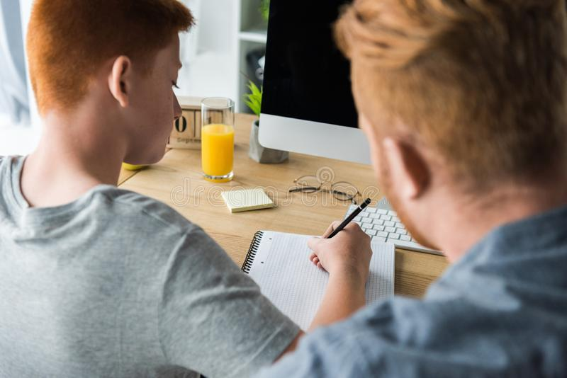 father helping son doing homework royalty free stock photos
