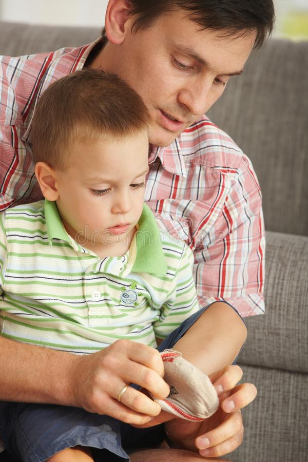 Father helping son putting on socks royalty free stock image