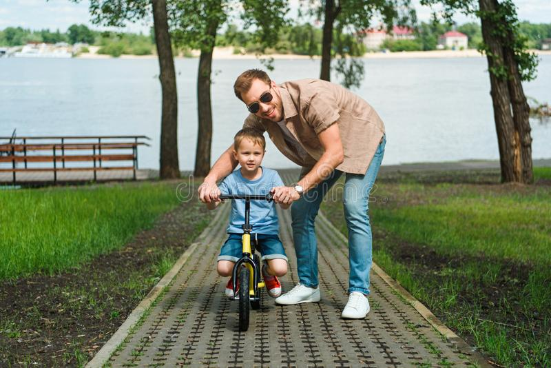 Father helping son riding small bike on road. Near river stock photo
