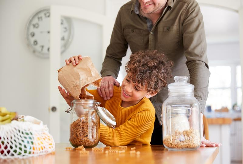 Father Helping Son To Refill Food Containers At Home Using Zero Waste Packaging royalty free stock image