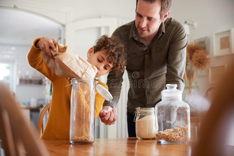Father Helping Son To Refill Food Containers At Home Using Zero Waste Packaging royalty free stock photography