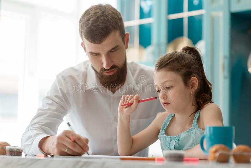 Father helps daughter with homework stock photography