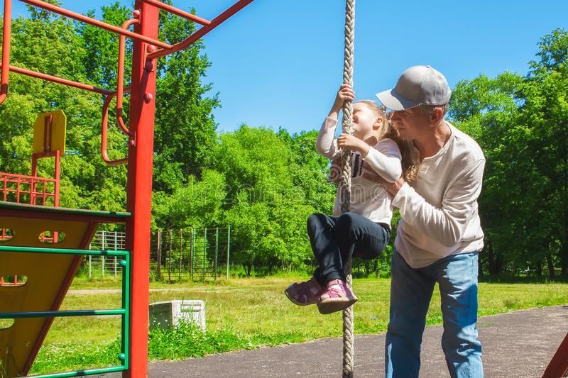 Father helps his child`s daughter to climb the rope. Concept of helping young people stock photo