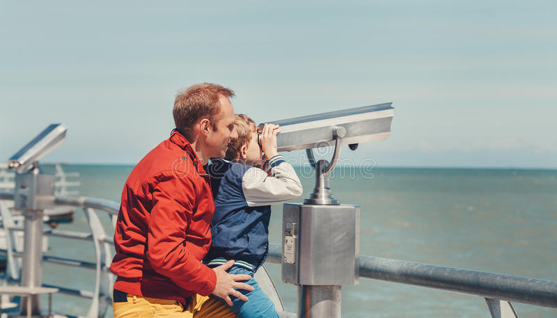 Father helps his little son to look in sea binoculars royalty free stock photography