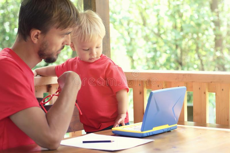 Father helps his toddler son learn to work on a toy laptop. Preschool education or home schooling concept. Copy space stock photo
