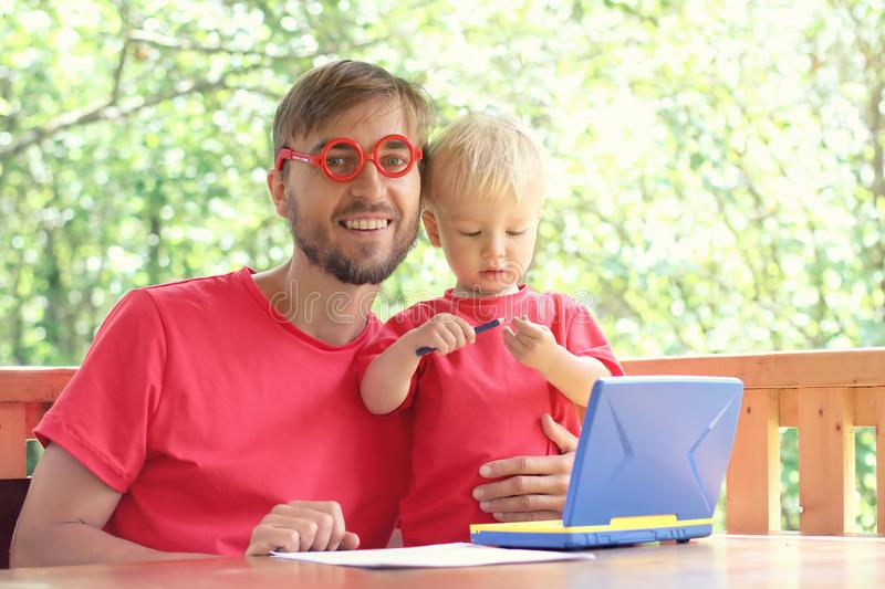 Father helps his toddler son learn to work on a toy laptop. Preschool education or home schooling concept. Copy space stock photos