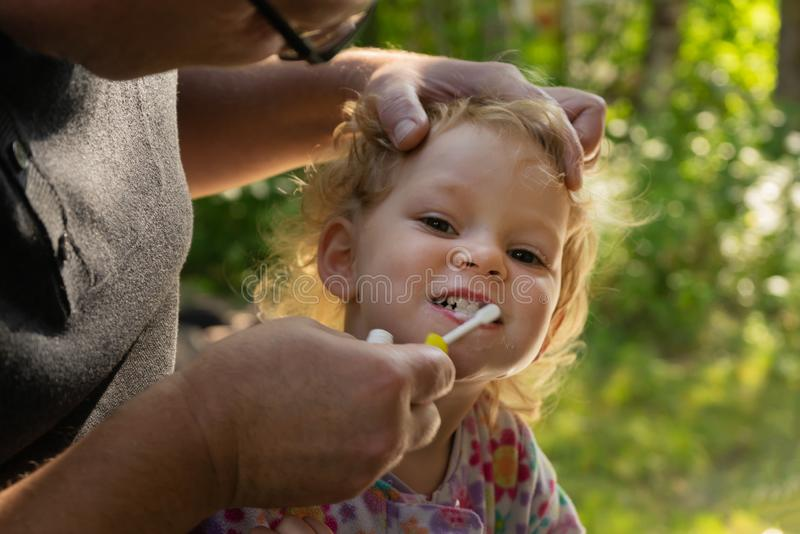 Father helps little daughter brush her teeth. royalty free stock image