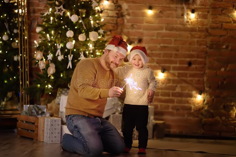 Father with her little son celebration Christmas with sparkler. In cozy living room in winter royalty free stock photo